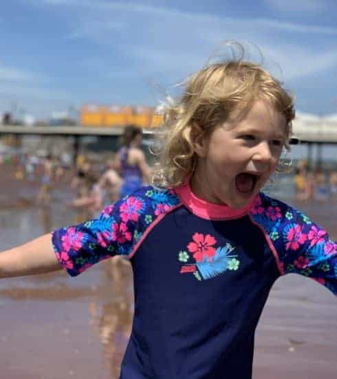 Child playing on Paignton beach in Devon
