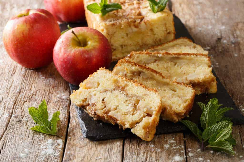 Sliced apple cake with apples on board