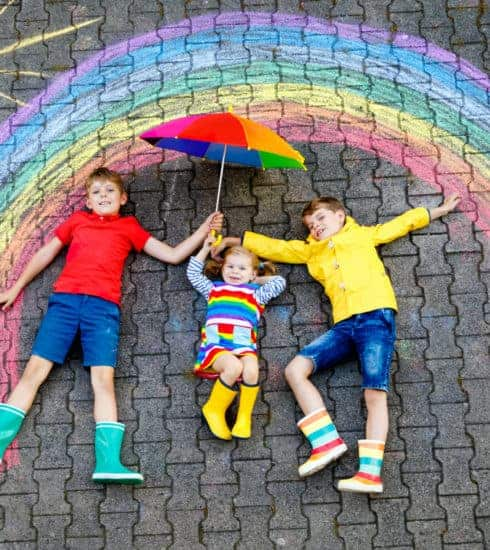 Children wearing colourful cloths laying on paving under a chalk rainbow