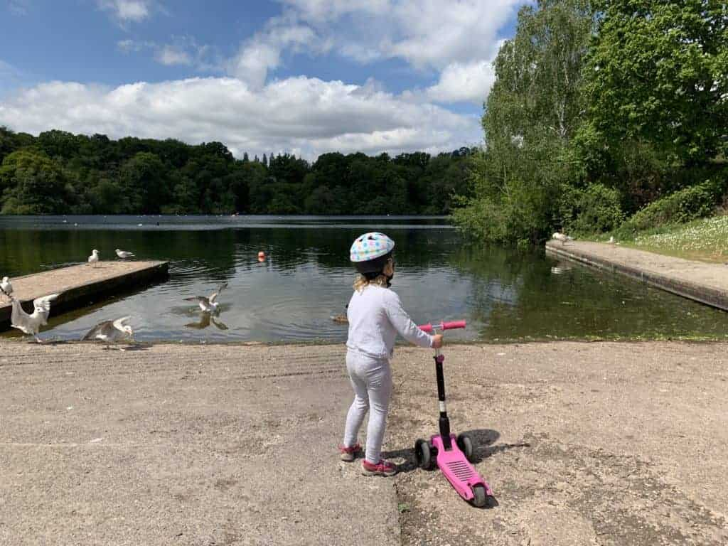 Child with scooter by lake at Decoy Park in Newton Abbot, Devon
