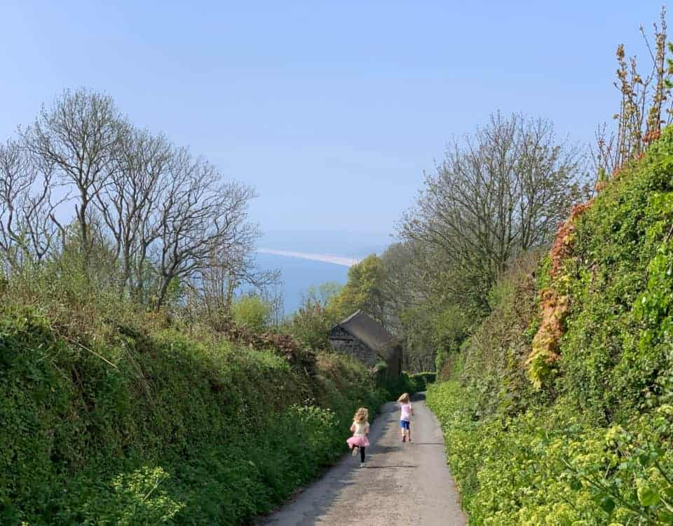 Children running down a Devon country lane towards the sea