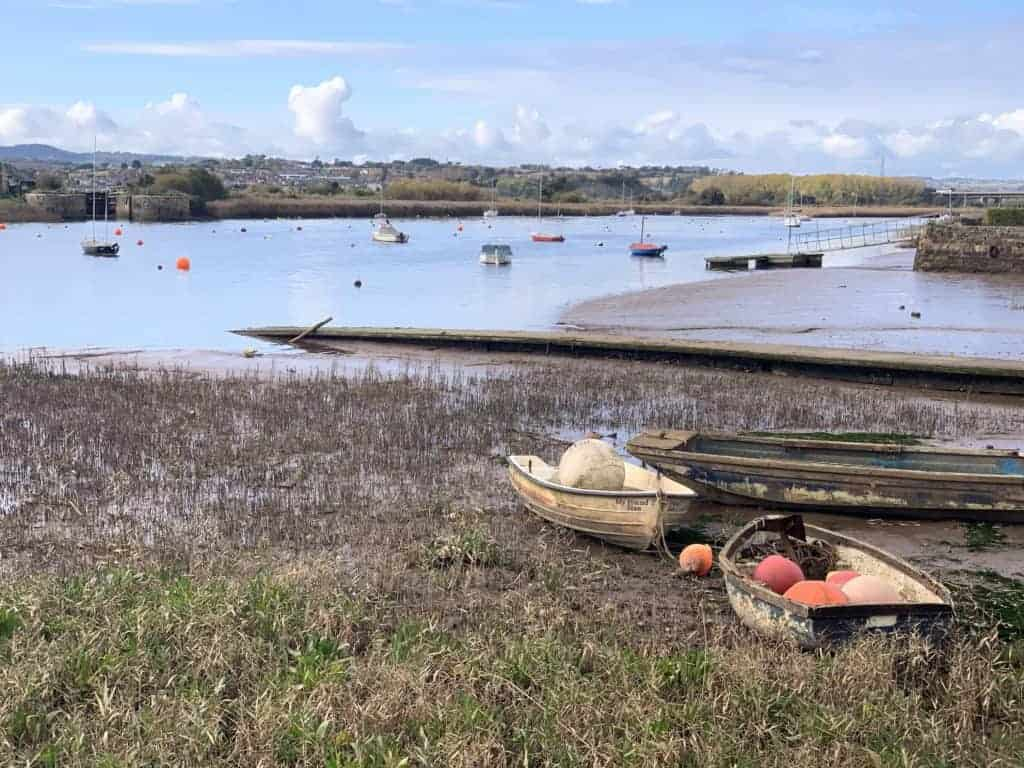 Fishing boats sit on the edge of River Exe at Topsham