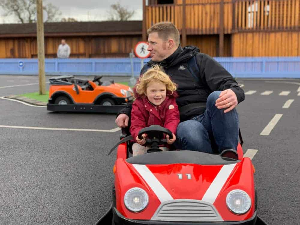Toddler in car at driving school at Crealy theme park, Devon