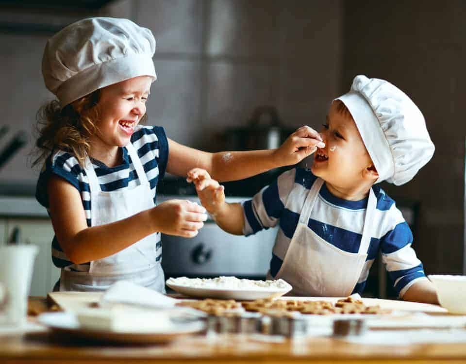 Happy kids baking a Devon recipe in their kitchen
