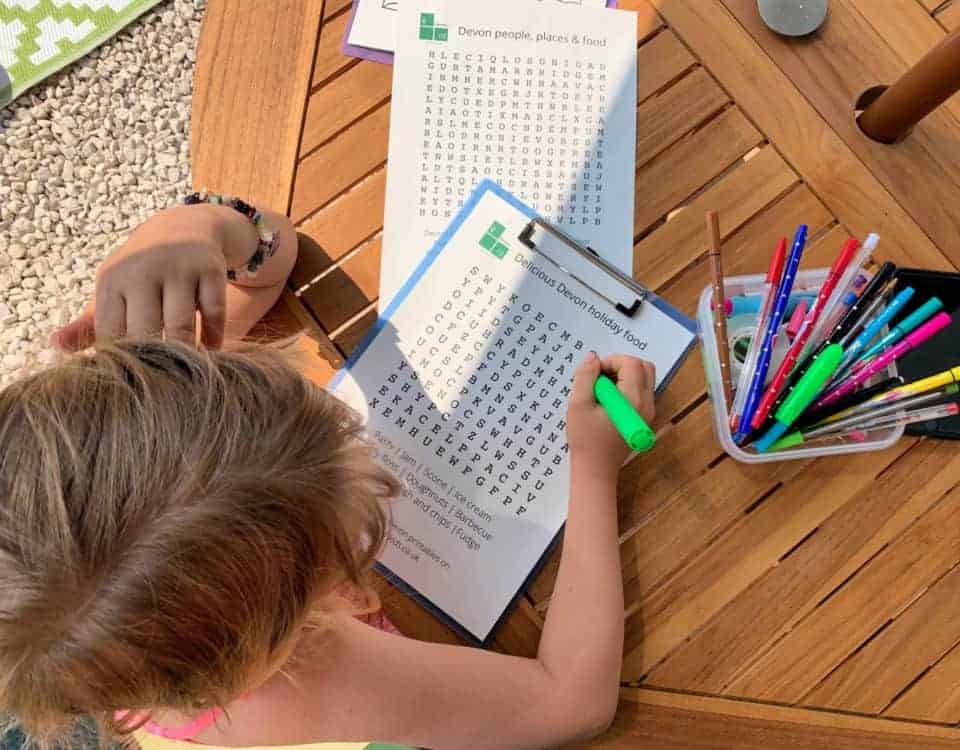Child doing a word search - Devon themed printable activities for kids