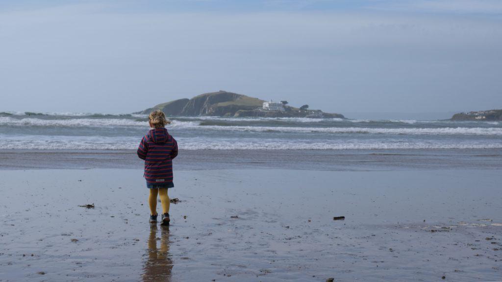 Child walking on sand at Bantham Beach overlooking Burgh Island