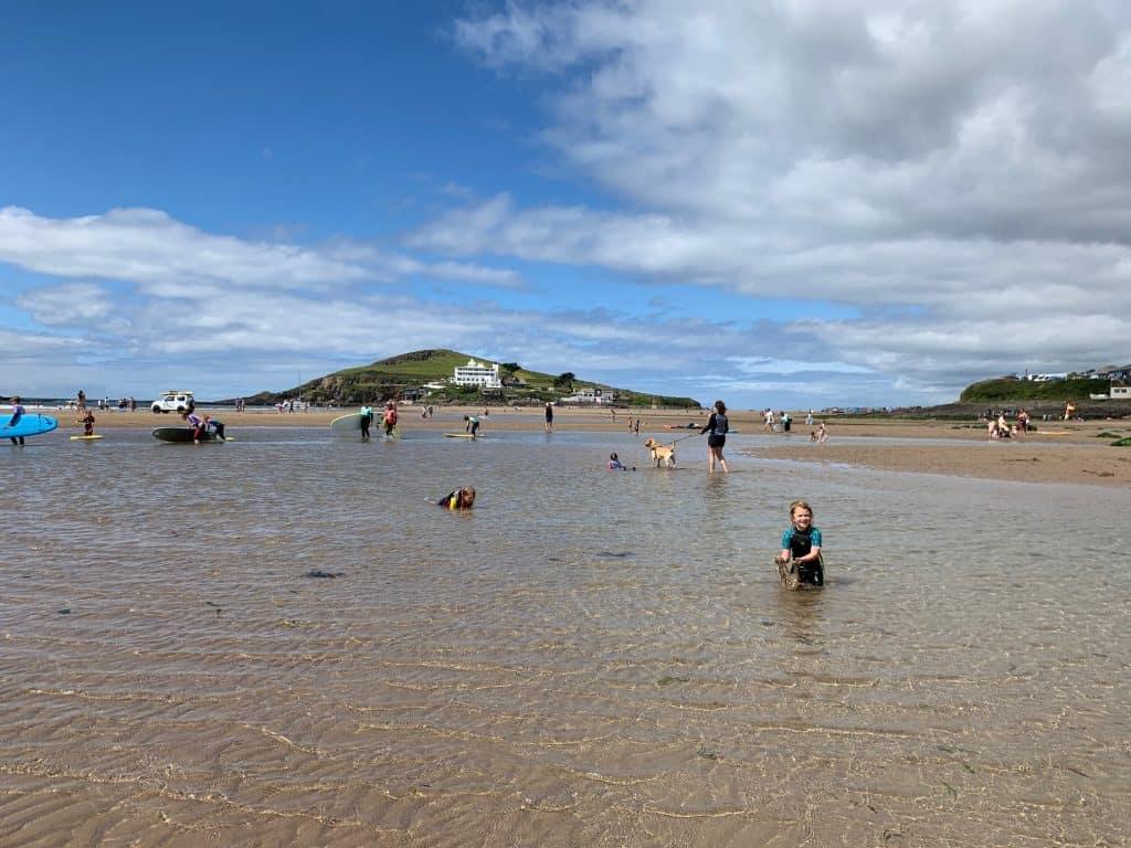 People enjoying Bigbury Beach with Burgh Island in the background