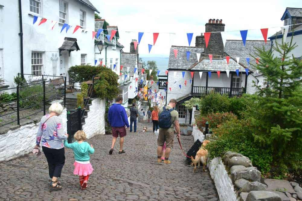Family walking down cobbled hill in the North Devon fishing village of Clovelly