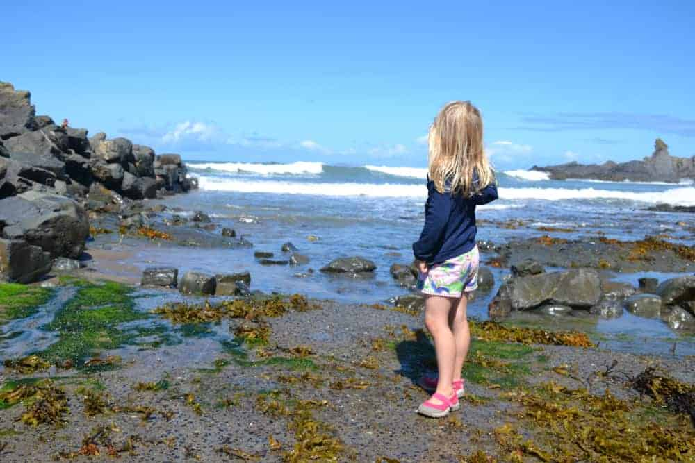 Girl standing on beach at Hartland Quay in North Devon