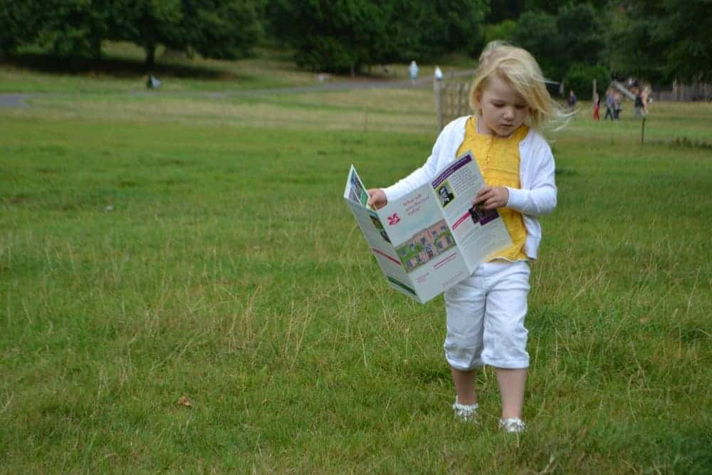 Child carrying guide to Killerton across parkland