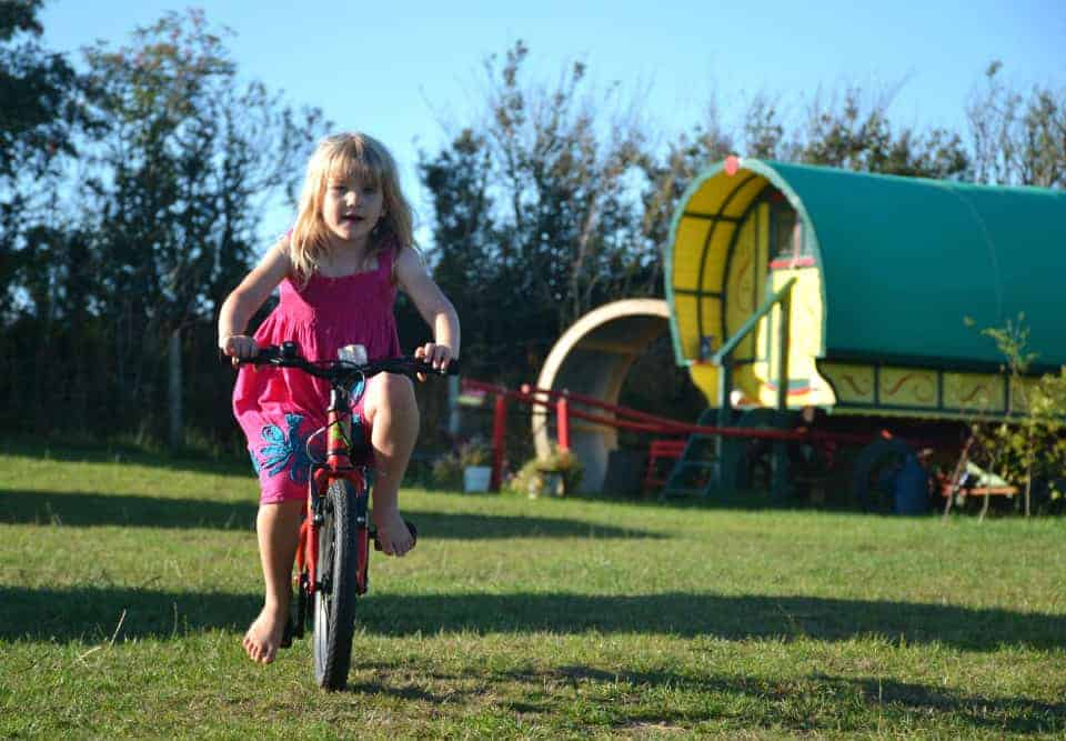 Child on bike at glamping site in Devon