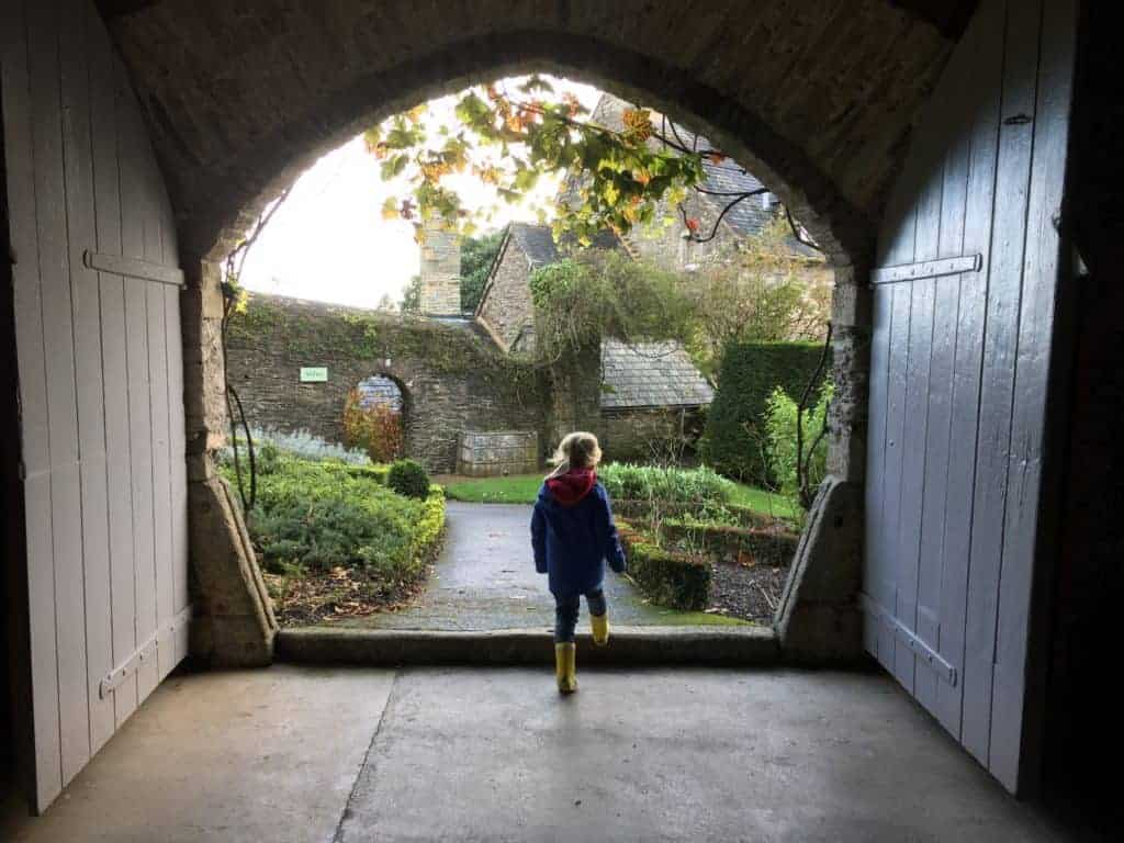 Child walking through doorway into garden at Buckland Abbey in Devon