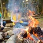 Cute little sisters roasting hotdogs on sticks at bonfire. Children having fun at camp fire. Camping with kids in Devon