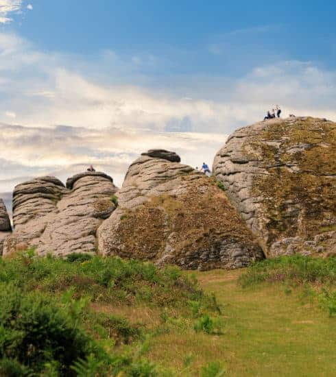 Families climbing a tor on Dartmoor in Devon, UK