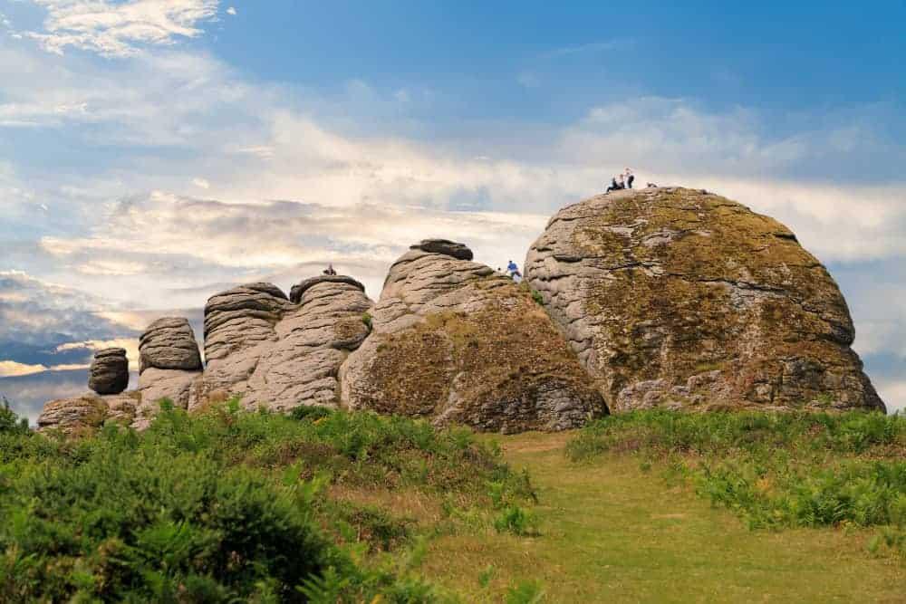 Families climbing a tor on Dartmoor in Devon, UK