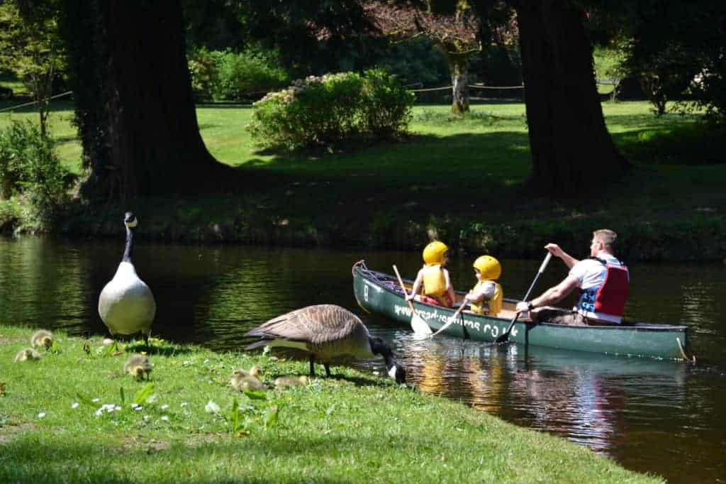 Family paddling canoe on lake at River Dart County Park