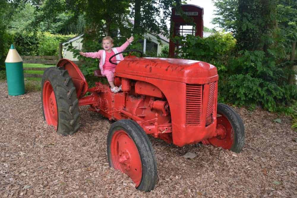 Child on tractor in playground at Woodovis campsite in Dartmoor