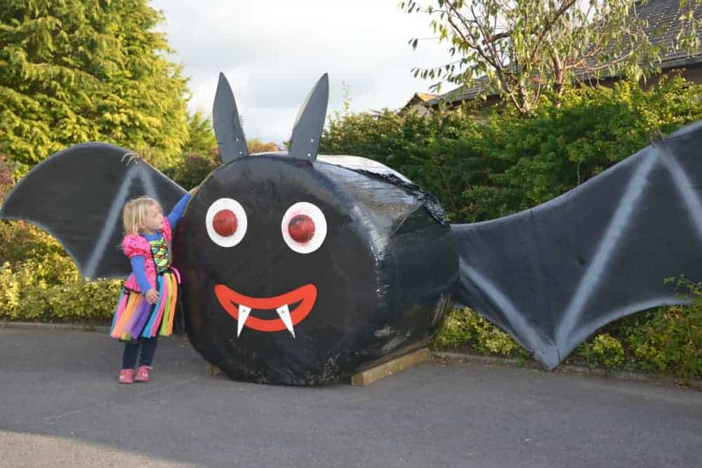 Child in witches costume stood with giant bat made from a covered hay bale