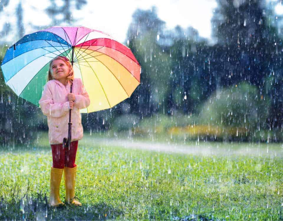 Child with rainbow umbrella standing in the rain