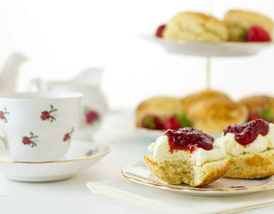 English Cream tea scene with scones, Devonshire style, with a bite taken out.