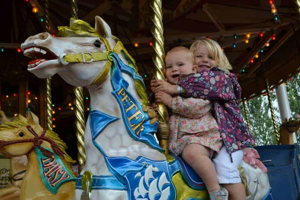 Girls on vintage horse carousel at Crealy