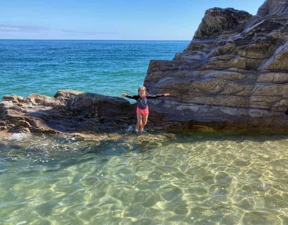 Child jumping into rock pool on Devon beach