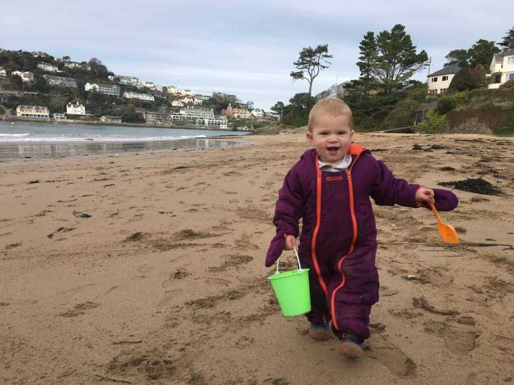 Toddler with bucket and spade on Mill Bay beach