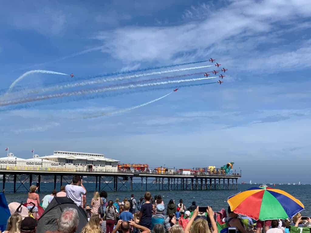 Red Arrows flying over Paignton Pier and beach in Devon