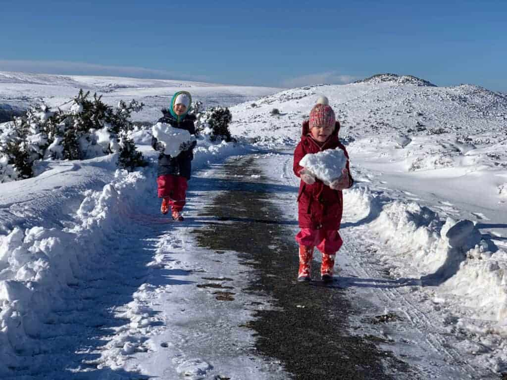 Children walking with blocks of snow on Dartmoor, Devon in Winter