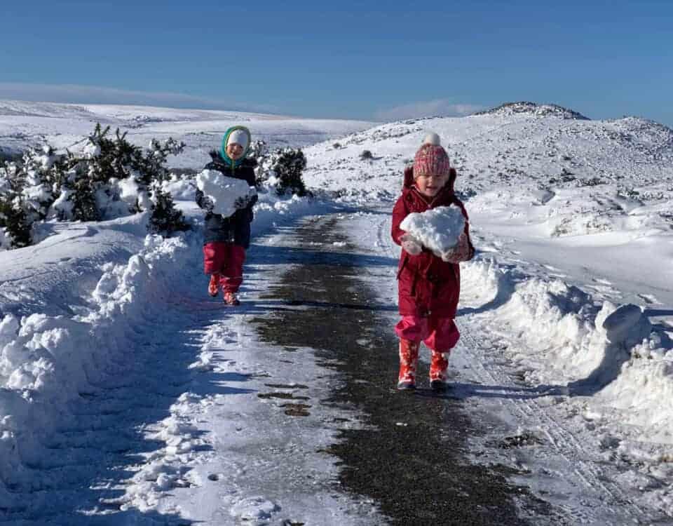 Children walking with blocks of snow on Dartmoor, Devon in Winter