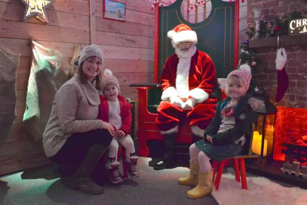 Family meeting Santa in grotto at Woodlands Family Theme Park in Devon