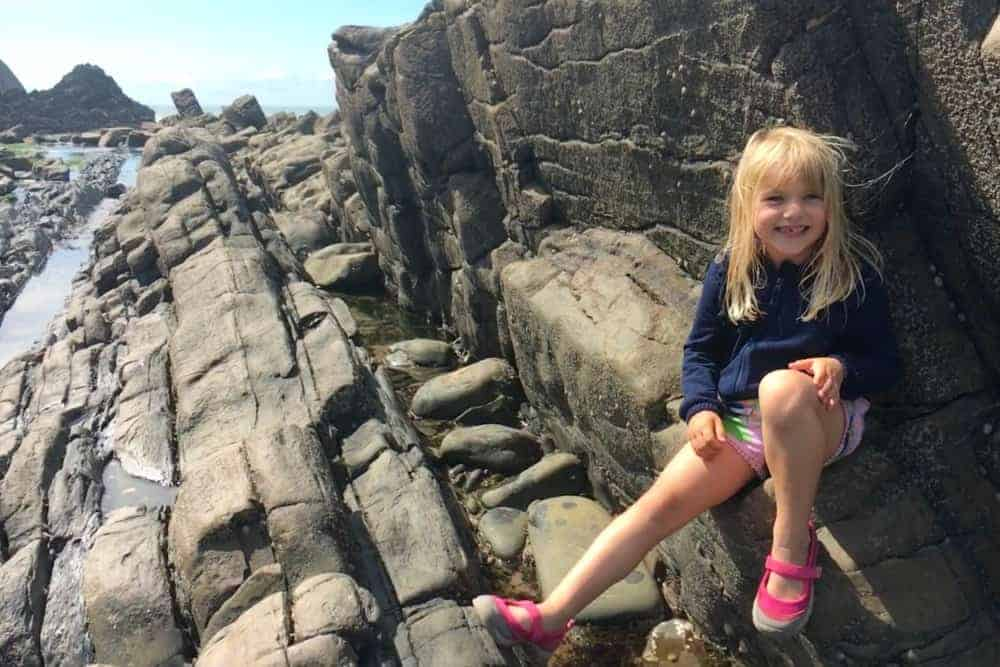 Child sitting on rocks at Blackpool Mill beach near Hartland