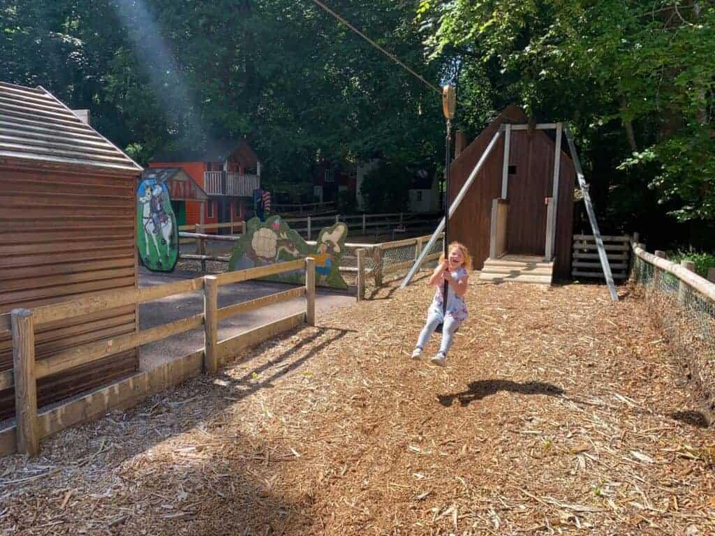 Child riding zip line in adventure playground