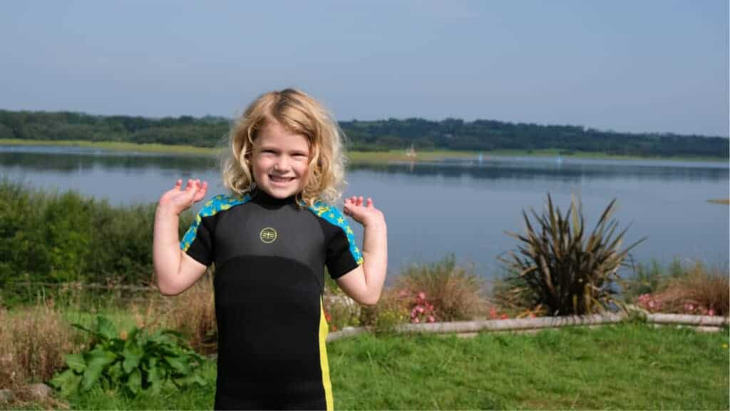 Girl in wetsuit standing in front of lake