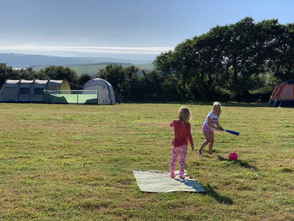 Children playing ball game on campsite field
