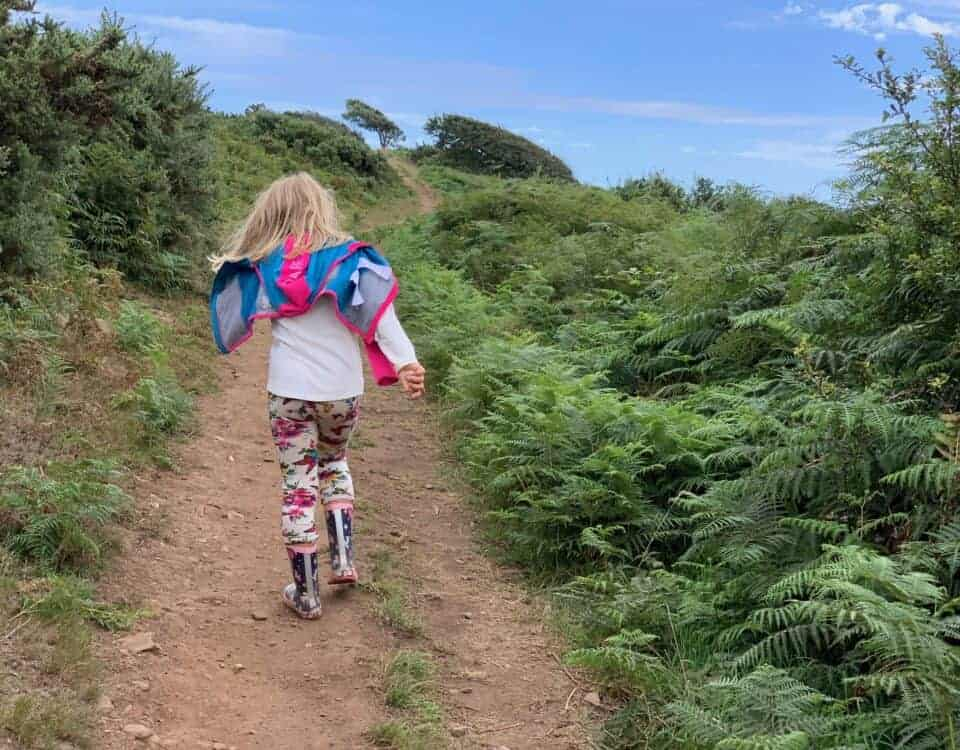 Child walking along South West Coast Path in Devon