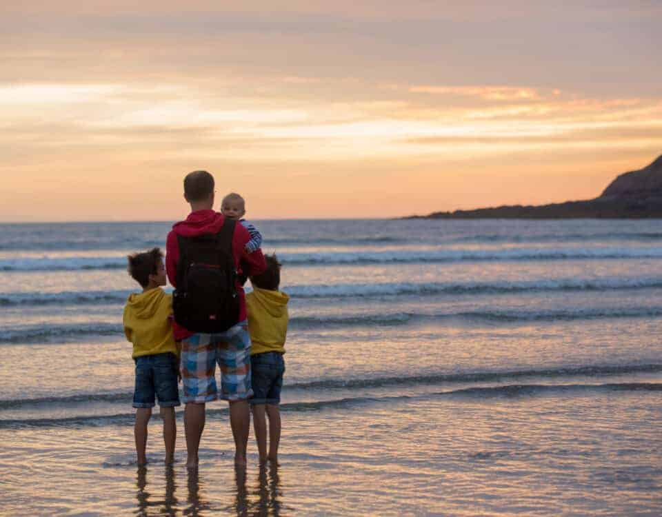 Young father with his beautiful children, enjoying the sunset over the ocean on a low tide in Devon, England
