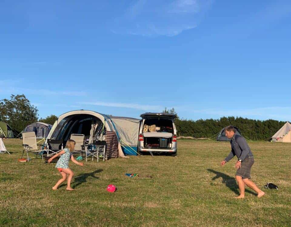 Family playing football in front of camper van and awning