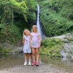 Kids standing in front of Whitelady Falls in Lydford Gorge