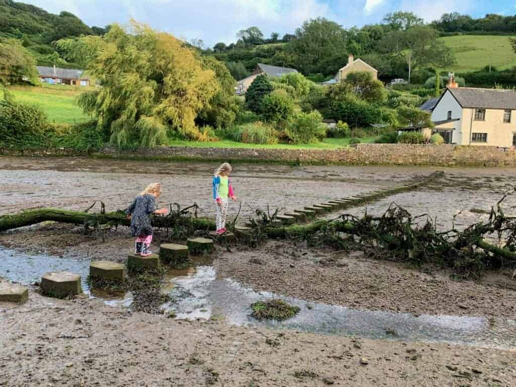 Children crossing stepping stones over a estuary creek at low tide