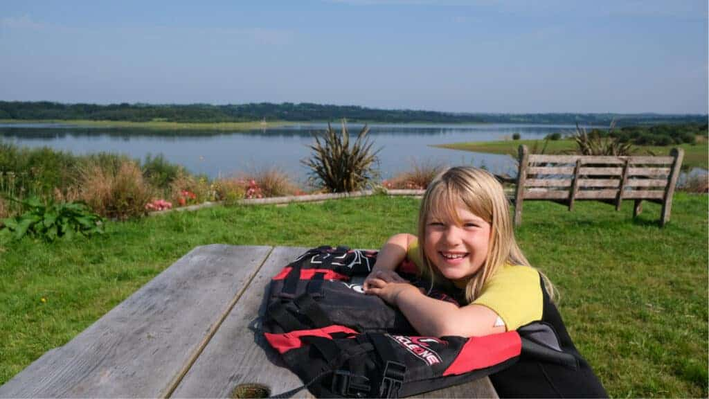 Child sitting at picnic bench by lake with buoyancy aid