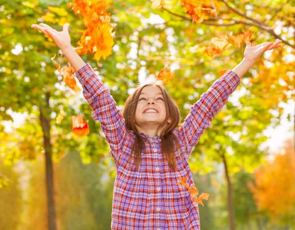 Girl throws orange leaves in the air in October autumn park