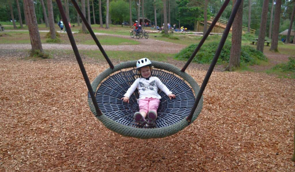 Child in bucket swing at Haldon Forest Park