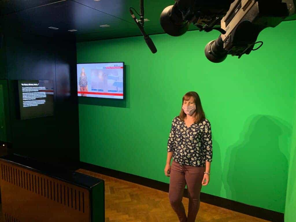 Helen from Twins, Tantrums and Cold Coffee presenting BBC Spotlight against a green screen in the Media Lab