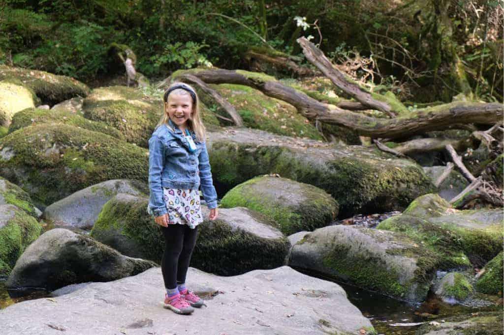 Girl stood on boulder at Becky Falls Devon