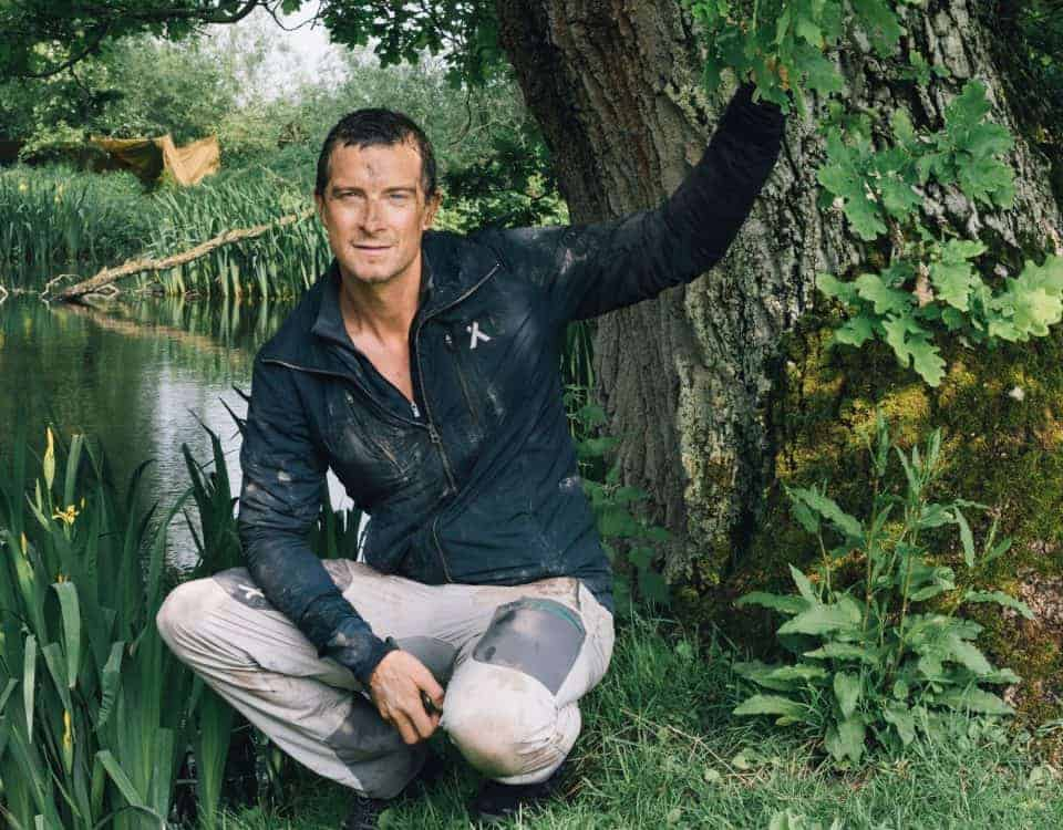 Bear Grylls crouch by tree