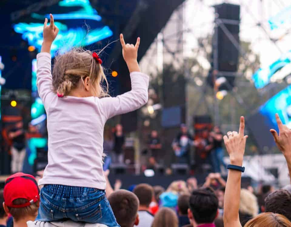 Kid on adult's shoulders at festival