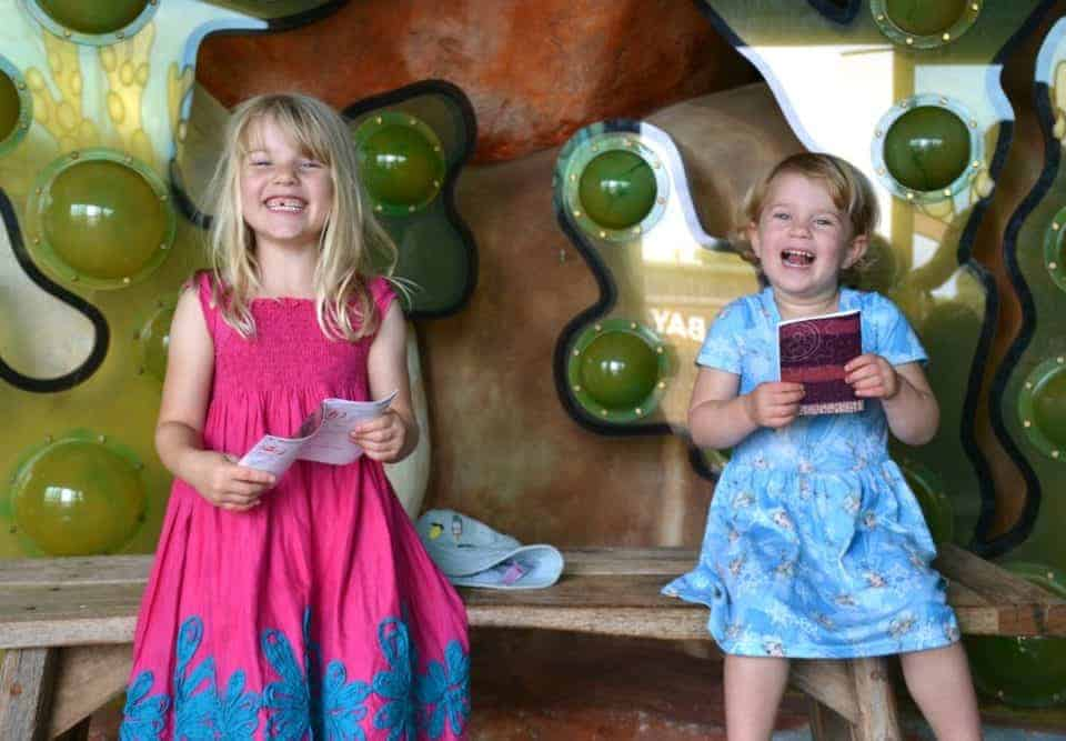 Sisters holding trail cards at Seaton Jurassic family attraction in Devon