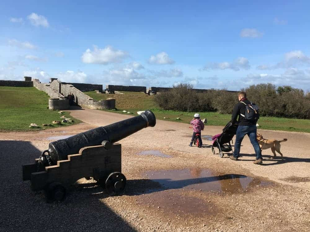 Family walking past a canon in fort 2 at Berry Head