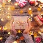 Top view of woman hands with gift box on wooden table.